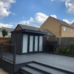 Composite Garden Building On A Raised Decking With A Matching Burnt Wood Grey Effect