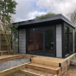 Composite Garden Building With Decking In Garden And Gravel Lacing The Ground