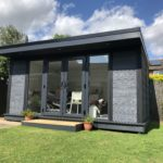 Side View Of Composite Garden Building With French Doors And Grey Panels
