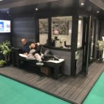 Upgraded Composite Garden Building Featured In Showroom With Staff Sitting On A Bench
