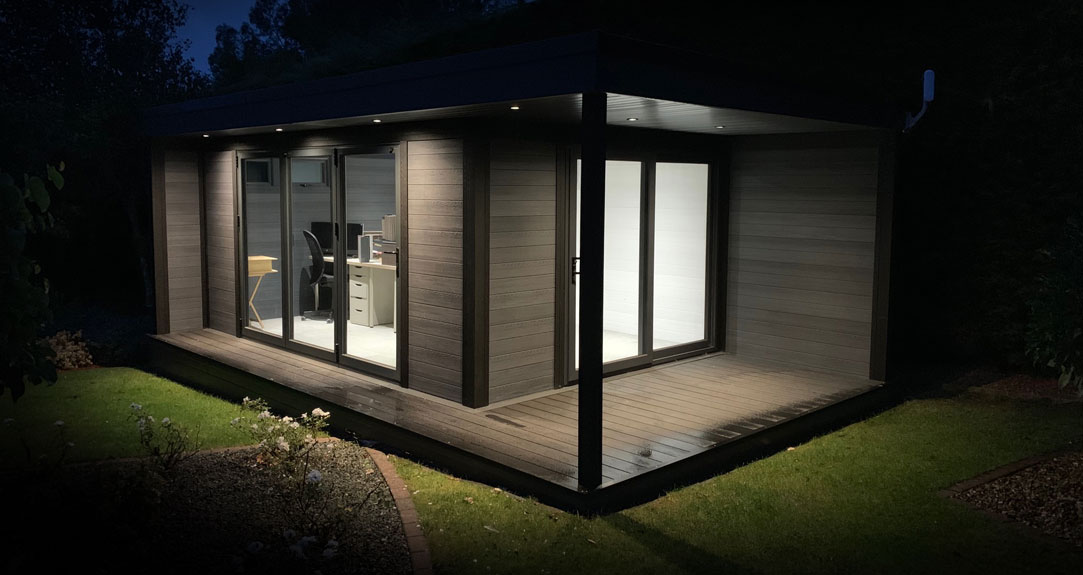 Composite garden room with lights on at dusk